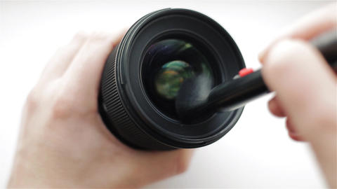 The photographer or videographer cleans front lens from dust and dirt at an Live Action