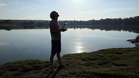Young man looks up and operates a drone on a lake bank in slo-mo GIF