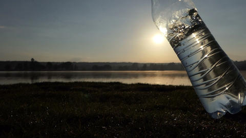 Plastic bottle with water is swayed on a lake bank at sunset in slo-mo Footage