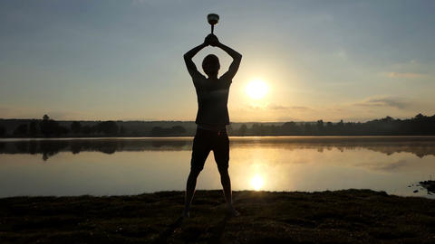 Inspired man raises his champion bowl on a lake bank at sunset Live Action
