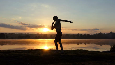 Young man does ballrom dance pas at a lake at sunset Footage