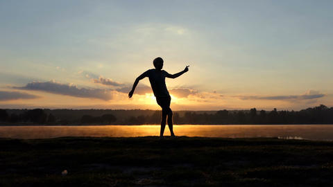 Stylish man dances free style on a lake bank at sunset in slo-mo Live Action