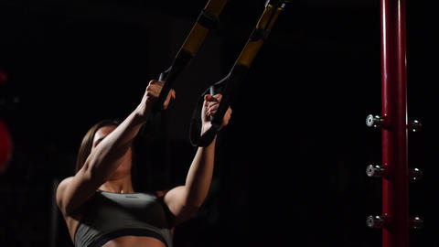 Young fit woman doing pull-ups on gymnastic rings. Muscular young female athlete Footage