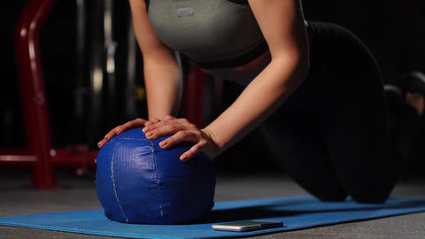 A brunette athletic builds push-ups on a mache in the gym putting a stopwatch on Footage