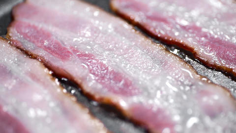 Pieces of tasty bacon is fried on the hot pan, hot boiling fat, cooking meat Live Action
