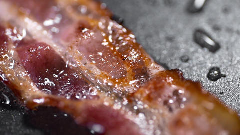 Crispy pieces of tasty bacon is fried on the hot pan in macro, hot boiling fat Footage