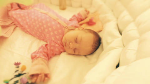 Cute newborn baby girl sleeping in her cot, time lapse Footage