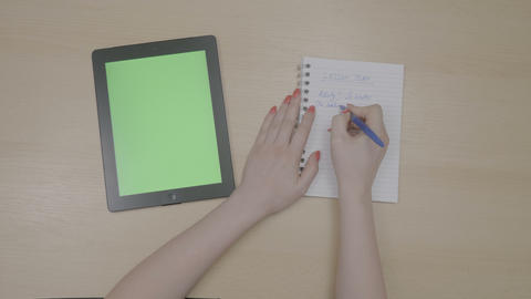 Top view of teacher woman hands planning lesson plan with green screen tablet pc Live Action