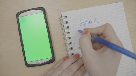Top view of female hands writing down necessary ingredients for recipe on Footage
