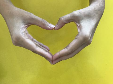 woman's hands make heart shape with yellow background Photo