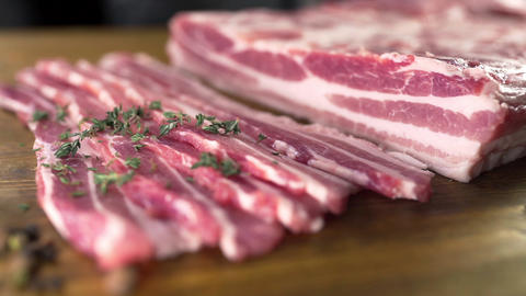 The cook sprinkles raw bacon by the cutted thyme, cooking meat, meals with meat Live Action