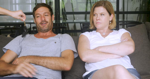 Someone hands keys over to a frustrated couple sitting on a sofa and they get Footage