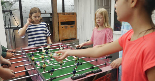 A group of young friends playing foosball games together boys against the girls Footage