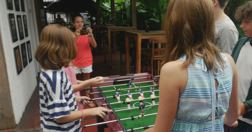 Young multi ethnic girl taking photos or video of her friends playing foosball Footage