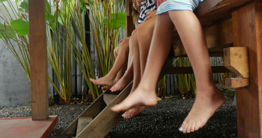 Diverse mixed racial group of young girls with bare feet and shorts swinging Footage