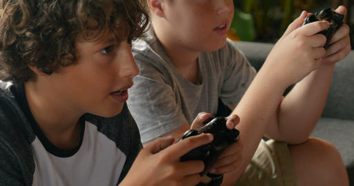 Close up of two young boys age 11 - 13 playing video games with hand controllers Footage