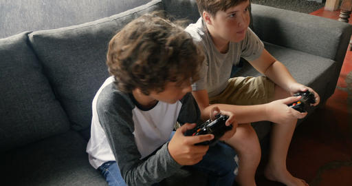 Two young 11 - 13 year old boys sitting on a sofa playing video games - Footage