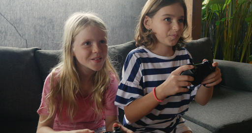 Two happy smiling young girls playing a video game together and talking while Footage