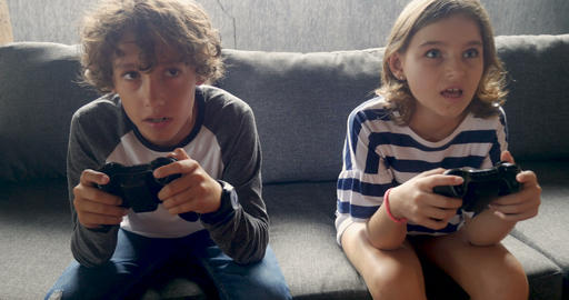 Push in of a young pre teenage boy and girl playing video games together Footage