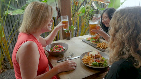 Three beautiful young women laughing and celebrating over a meal and drinks in a Footage