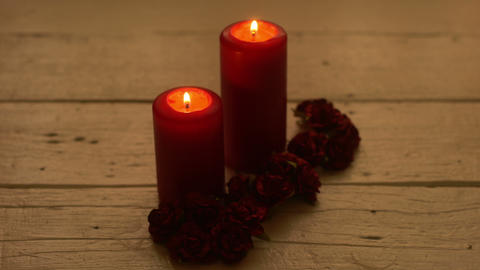 Red candles light with rose on white wooden desk GIF