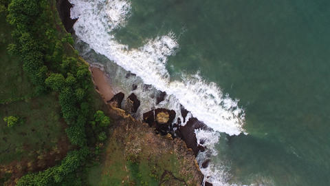 Aerial video of waves breaking into a cliff ( Bali , Indonesia ) Footage