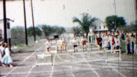 1958: High school boys track race hurdles event finishing line Footage