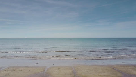 Boundless Ocean Washes Beach under Blue Clear Sky Live Action