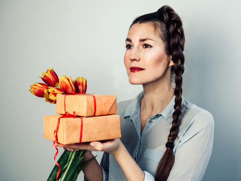 Happy woman with gifts and a bouquet of flowers フォト