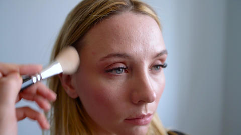 make-up artist applies powder and makes the correction of the face shape to the Footage