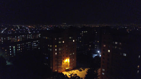 View from the height to the illuminated night city, multi-storey houses. Ukraine Footage