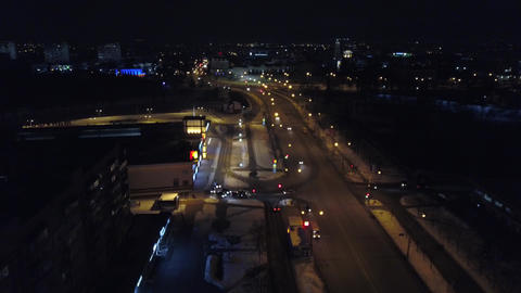 View from the height to the illuminated busy road and night city, multi-storey Footage