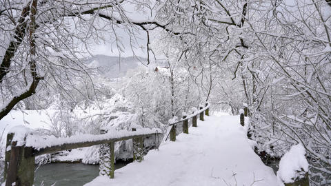 Young woman walks across the bridge across the river. Beautiful winter snow Footage