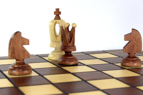 Оn the chessboard the queen and two horses announced checkmate to the white フォト