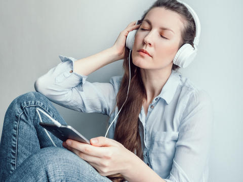 Stylish woman in headphones listening to music フォト