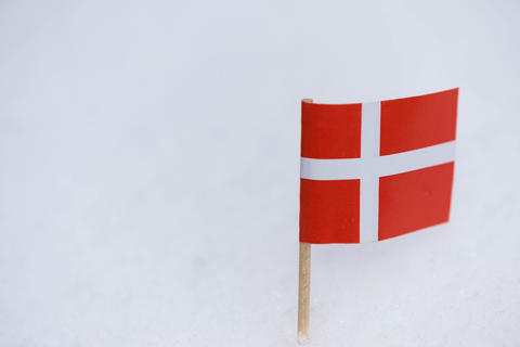 Denmark flag made from paper with brown toothpick on white snow background フォト