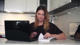 Beautiful young business woman working at a computer with a diary Footage