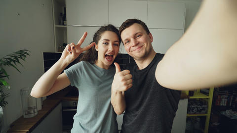 POV of Young funny couple taking selfie photos with smartphone camera standing Footage