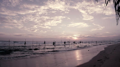 Fishermen on traditional fishing SriLanka poles near the shore in Indian ocean Footage