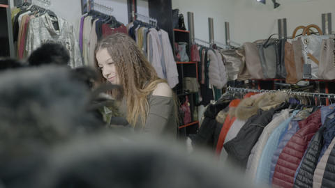 Stylish customer girl choosing basic pieces of clothing for her autumn winter Footage