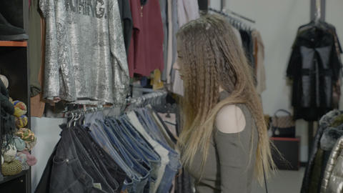 Cute young woman looking for shoes and clothes to buy shopping in a thrift shop Footage