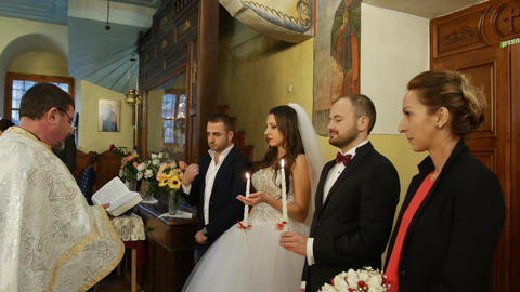 Married couple with sponsors and priest during wedding ceremony in church Footage