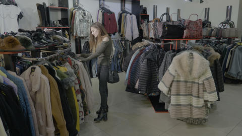 Excited young teenager girl doing shopping on her free time in a small shop Footage