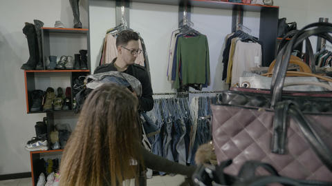 Brother goes out to shop with his sister and helps her holding the clothes she Footage