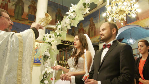 Christian wedding ritual ceremony in a church with priest and young family Live Action
