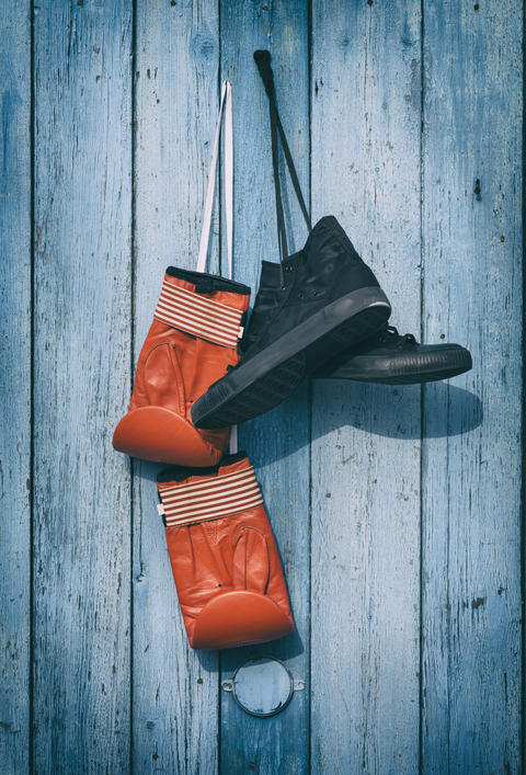 Black textile worn sneakers and red leather boxing gloves Photo