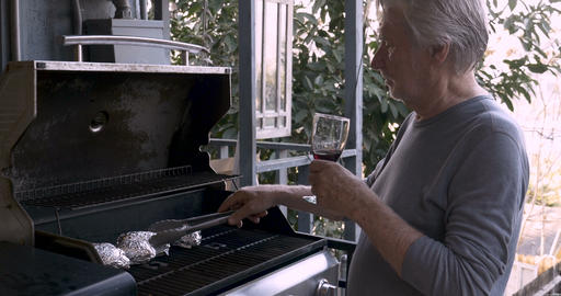 A man with long hair cheers an elderly man in his 70s grilling on a barbecue Footage