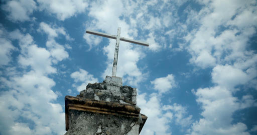Time lapse of the clouds moving by an old cross against a blue sky Footage
