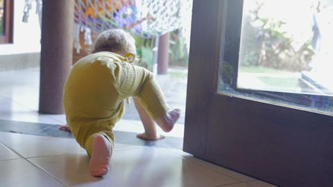 Baby crawls to the edge of a ledge, sits, and turns to look behind her in slow Footage