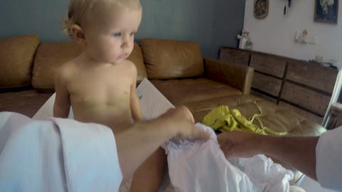 POV of a father dressing his young baby girl in a white dress at home Footage